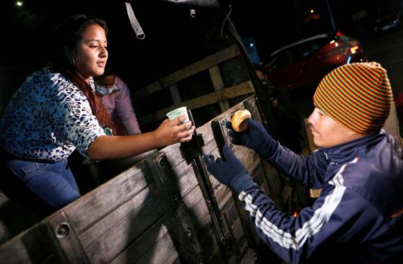 Colombians give food to Venezuelan migrants at the Rumichaca International Bridge, in Tulcan